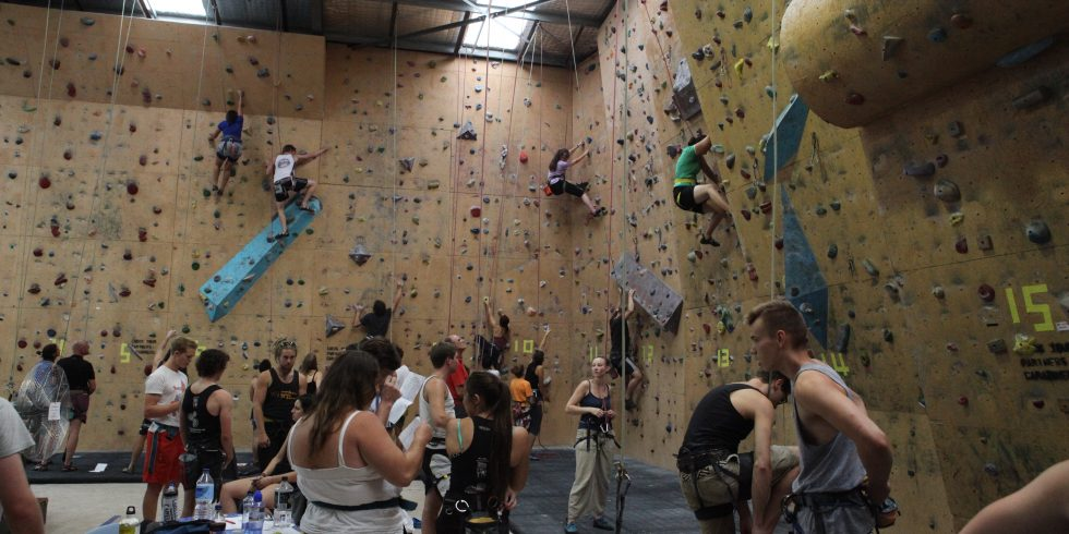 The gym is full of climbers competing.