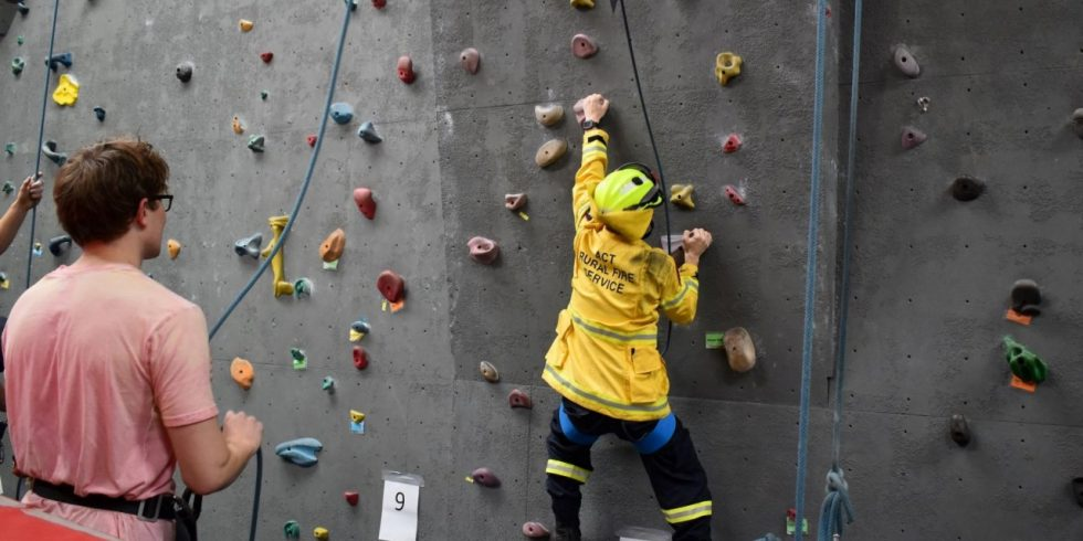 A member of the Rural Fire Service climbs in one of our gyms in full, bright yellow firey gear.