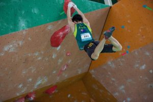 Jun Park clings to a hold with both hands in a national climbing competition.