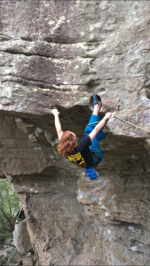 Liam McIntyre lead climbs on an outdoor rock face.