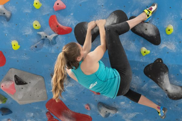 An image of Lis Andres climbing a bouldering problem, placing a high heel hook over her head on a climbing hold. She is wearing the La Sportiva Women's Skwama technical climbing shoe, the subject of her recent gear review.