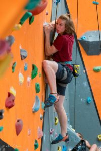 A climber in one of our gyms eyes his next move as he grips a hold with both hands.