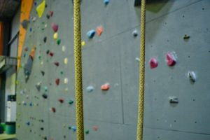 A close up of one of our ropes in the gym, with a large climbing wall covered in colourful holds in the background.