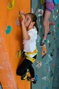A young girl climbing one of our walls looks closely at the next hold as she reaches for it with her left hand.