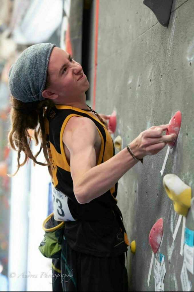An image of Sam Inglis climbing during the ACT State Boulder Titles. His face is scrunched up in pain as he clings to a small hold with just two fingers.