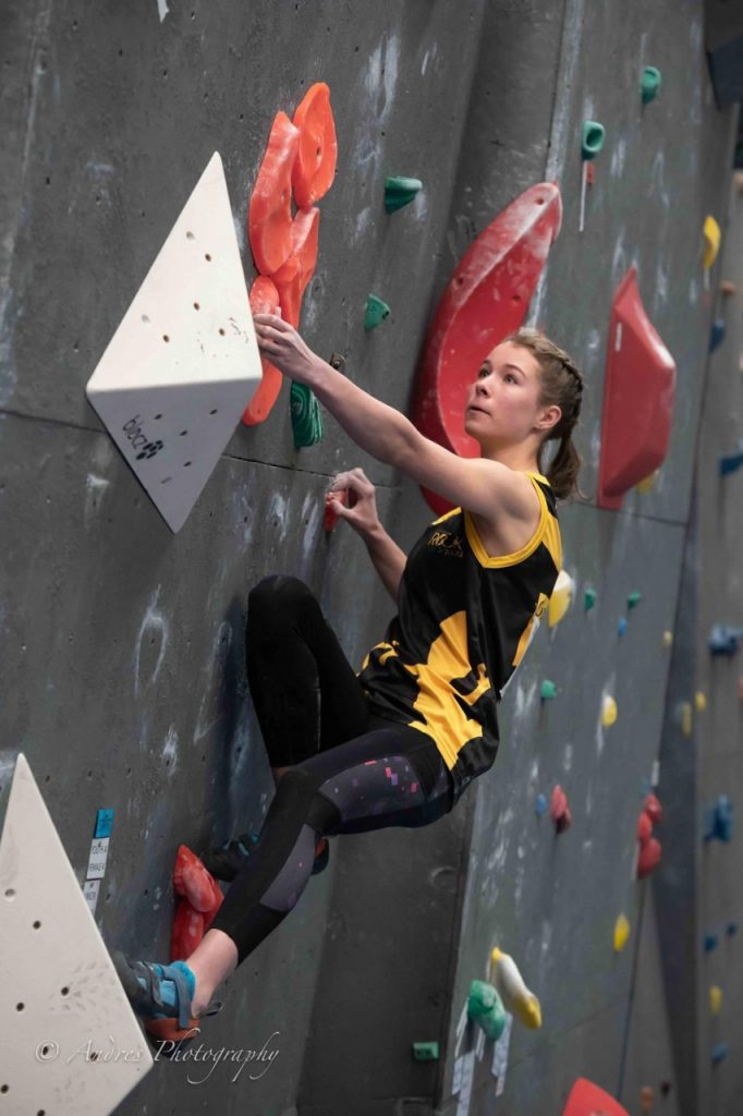 A young woman climbs at one of our gyms in the 2019 ACT State Boulder Titles. Her gaze is intensely focused on her next move.