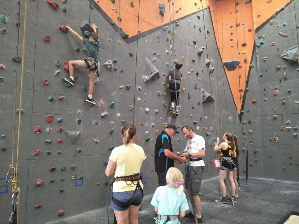 The owner of the gyms helps a man learn how to belay, as other people climb around them.