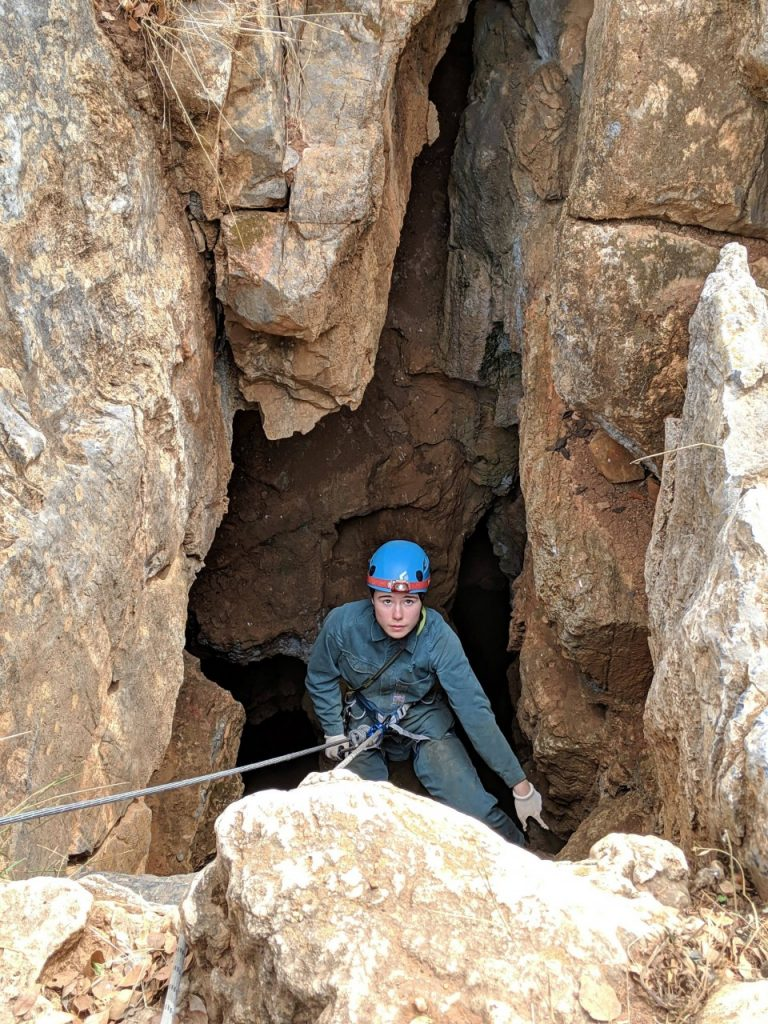 A young woman wearing full-body overalls and a helmet with a headlamp begins abseiling in the mouth of a large cave.