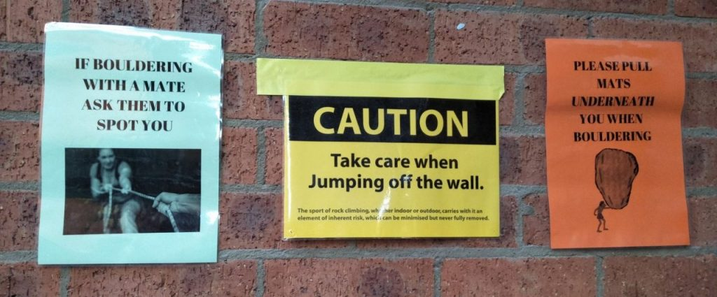 "A photo of some of the signs posted on the wall near the entrance of Hume's bouldering caves. Signs read: ""If bouldering with a mate ask them to spot you,"" ""Caution. Take care when jumping off the wall,"" and ""Please pull mats underneath you when bouldering."""