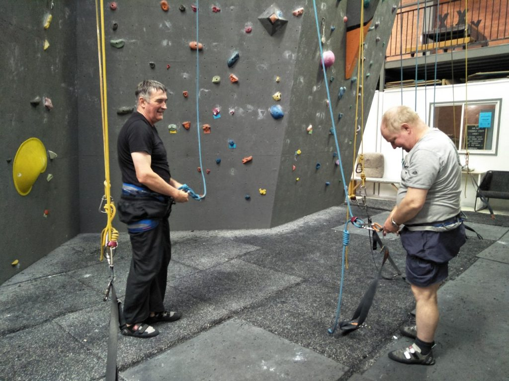 Two men talk to each other and disconnect themselves from the ropes after one of them finished a climb. They are both smiling