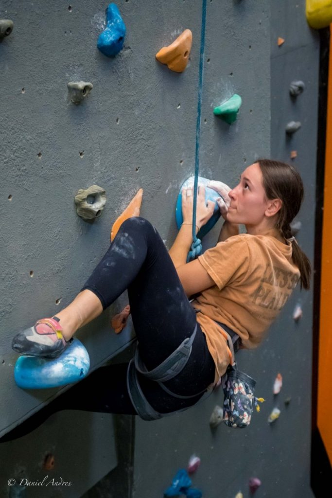 A person wearing an orange t-shirt, black leggings, and climbing gear climbs one of our walls during a competition. They are pulling themselves up over and overhang, with two hands on one hold and looking up at the next hold.