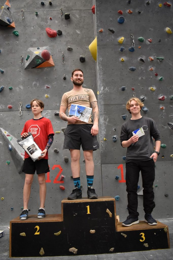 Three competitors from the Men's C category stand on the winners podium in first, second, and third places, holding their prizes up for the crowd to see.