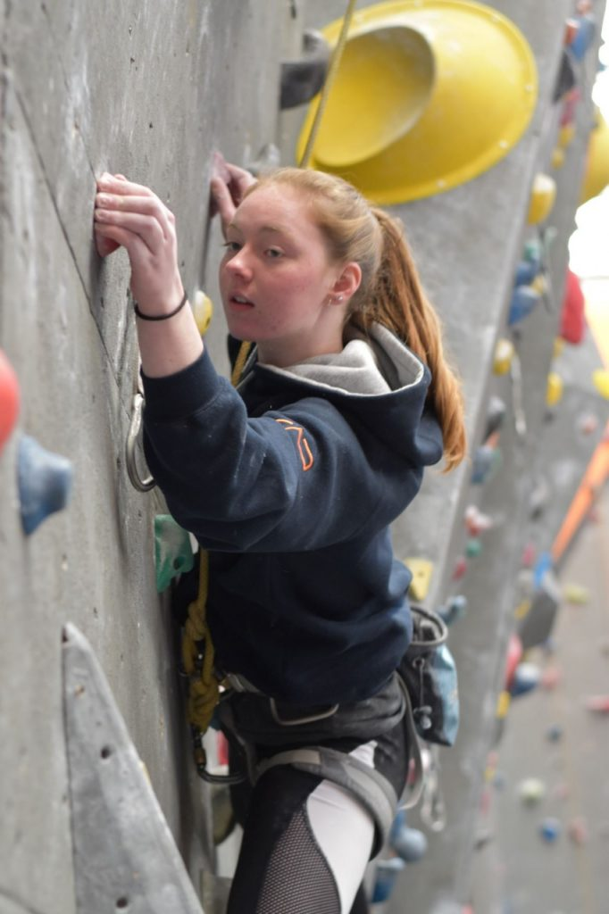 A close up photo of Cait James leaning across a wall and reaching to pinch an orange hold with her left hand. Her mouth is slightly open and her gaze is focused on the hold she's grabbing.