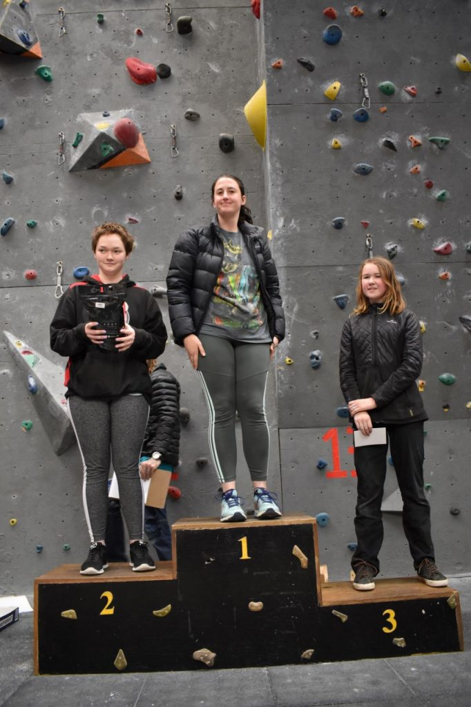 Three competitors from the Women's C category stand on the winners podium in first, second, and third places, holding their prizes up for the crowd to see.