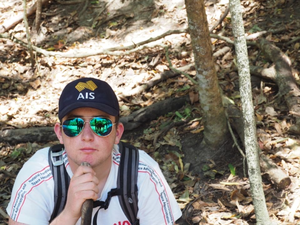 A bust shot of Eoin on a hiking trail with his chin resting on the top of a walking stick. He's wearing an AIS cap and green reflective sunglasses.