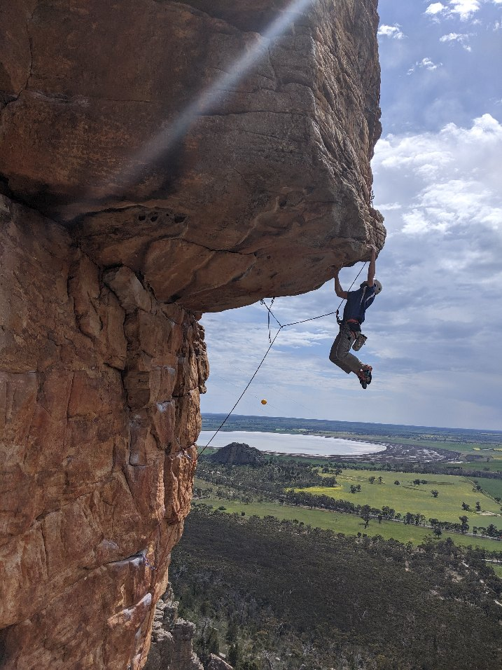 Sam Sykes hangs off the edge of a cliff roof in the Arapiles by two hands, his legs dangling below him as he looks up at his next move. He is leading the route. Forest, farmland, and a large lake are visible in the background.