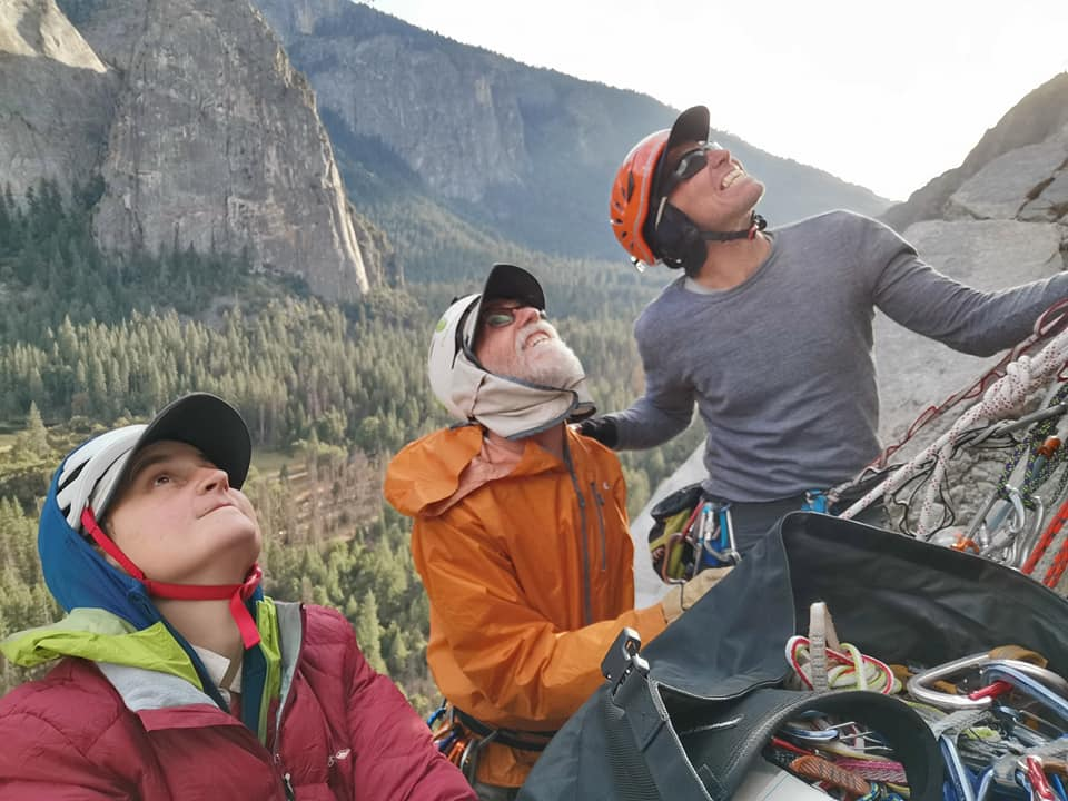 Cait, Peter, and Greg look up from the bottom of El Cap wearing helmets and climbing gear, with a large bag of gear in front of them.