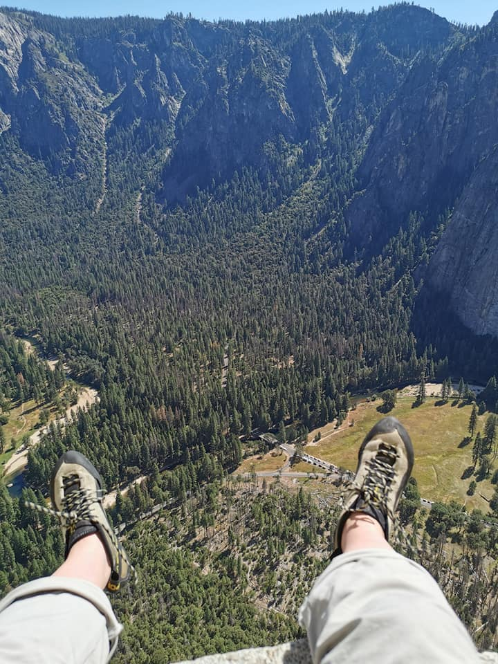 A photo of Cait's feet in climbing shoes dangling off a ledge with a sweeping view of the pine-forested valley below.