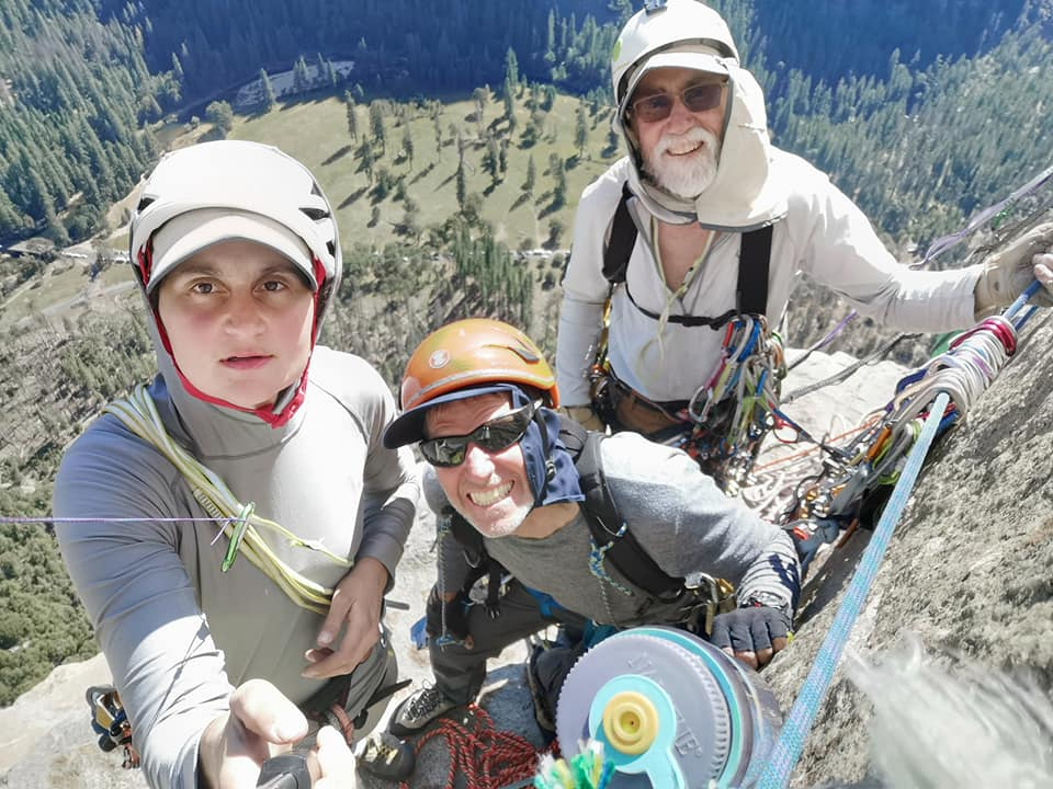 A selfie looking down at Cait, Greg, and Peter standing on a ledge on the side of El Cap with the valley below them.