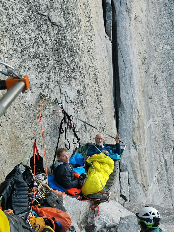 Greg and Peter rest on a portaledge dangling off the side of El Cap together in sleeping bags. Peter holds up a peace sign.