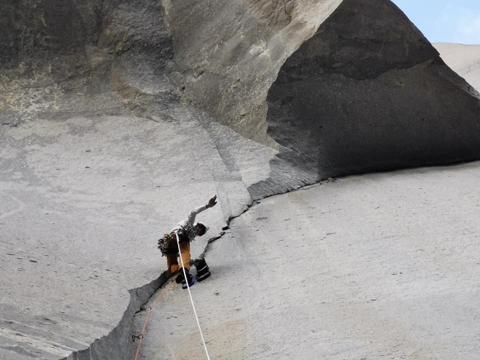 A photo looking up at Peter as he leads a pitch along a crack below a large overhanging roof. He looks down at the camera and waves.