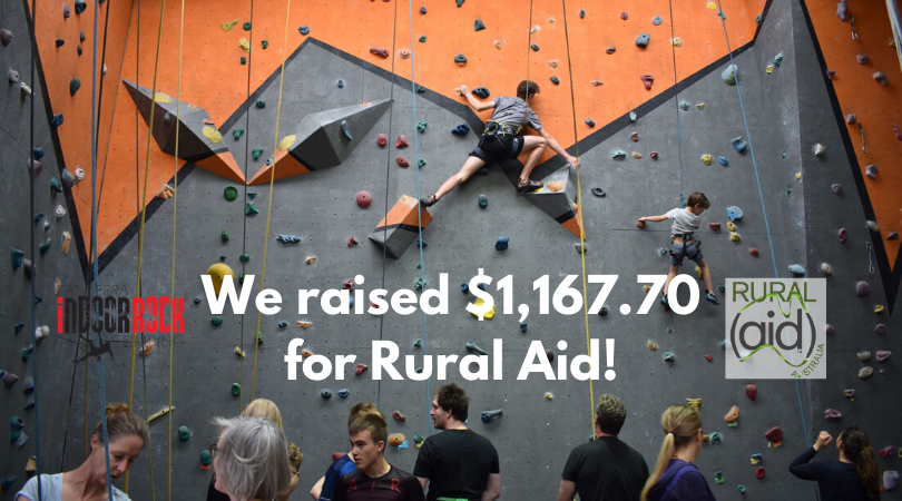 "A crowd of people mill about the floor of the gym while a few climbers work on some routes during the competition. Image text reads: ""We raised $1,167.70 for Rural Aid!"""