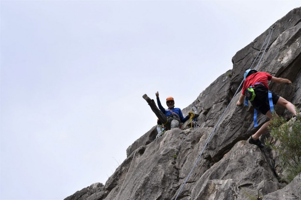 Secured into the side of a cliff face and standing on a ledge, Armando smiles, holds out a thumbs up, and kicks one leg into the air. A climber ascends a route nearby.