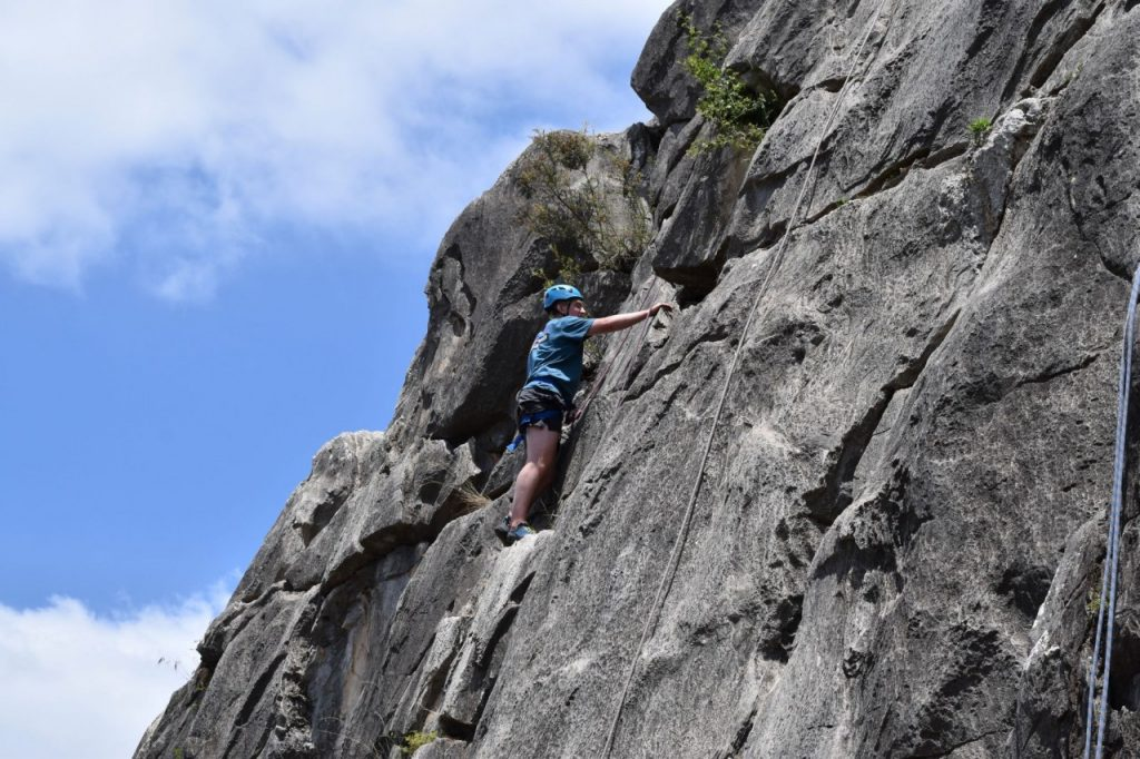 A young man ascends a climbing route on the side of a cliff.