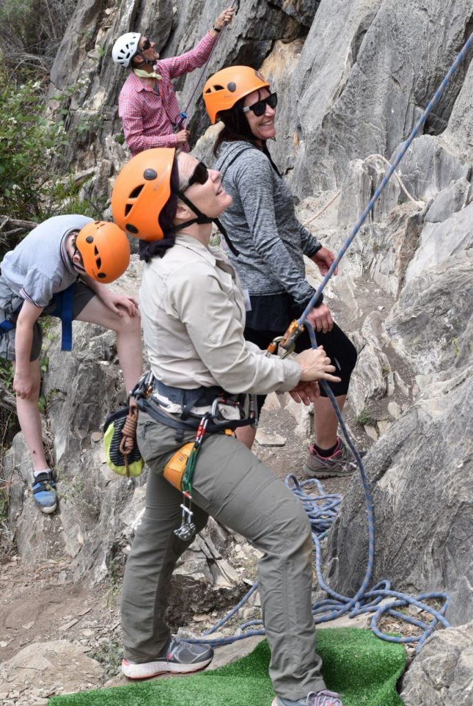 Three guides and a climber stand at the base of a cliff, looking up at the climbers they are belaying and smiling.