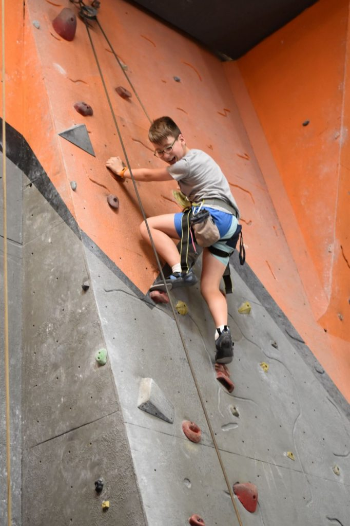 A young boy looks down at his belayer and yells something down with a smile as he climbs a route in one of our gyms.