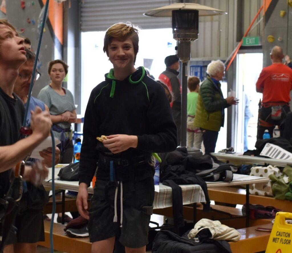 A photo of Joseph standing in the middle of a busy gym during a competition and smiling at the camera.