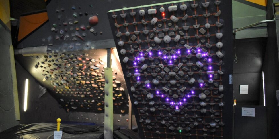 A photo of the Tension Board at Mitchell and the adjacent steep training cave. The Tension Board lights make a pink heart.