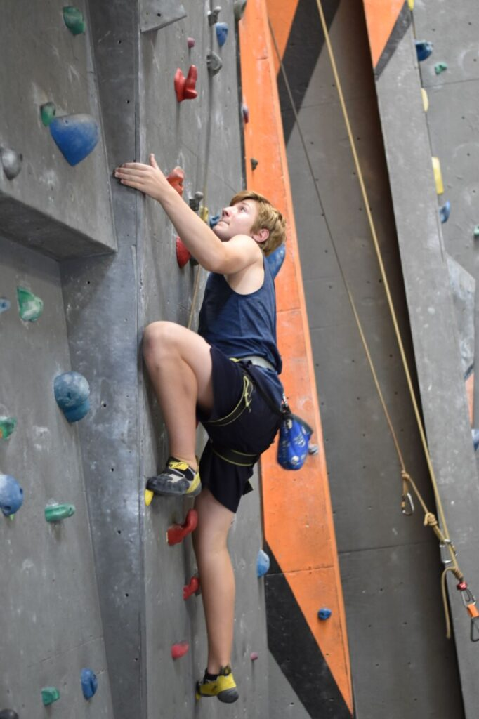 A photo of a boy in our elite Rock Squad climbing at Mitchell. He is staring at the next hold with a concentrated expression.