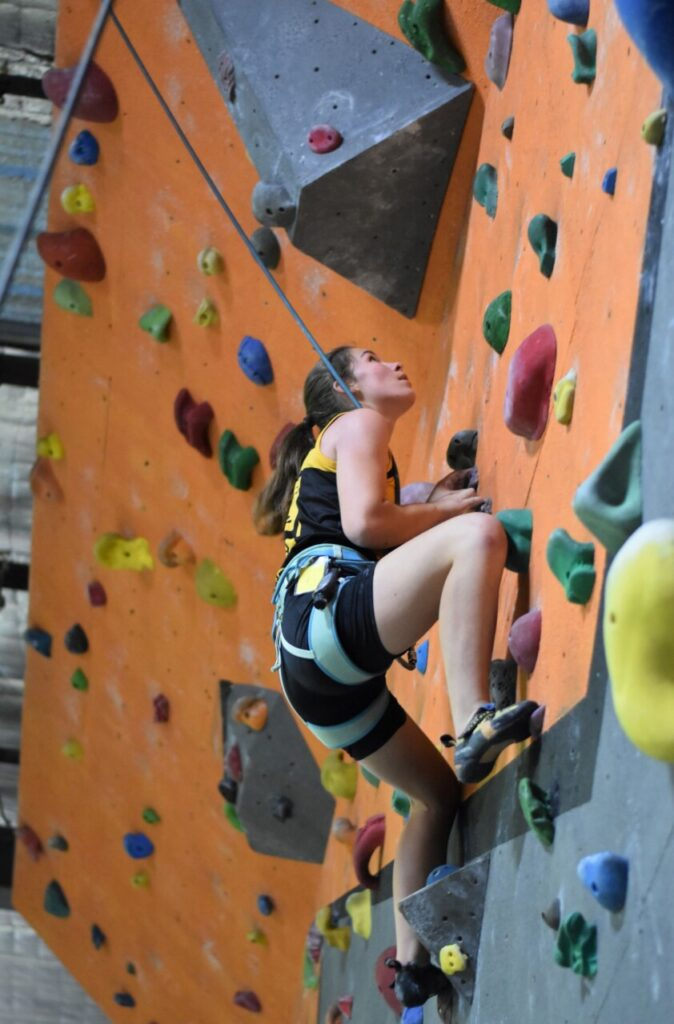 A photo of a young woman in our elite squad climbing on top-rope.