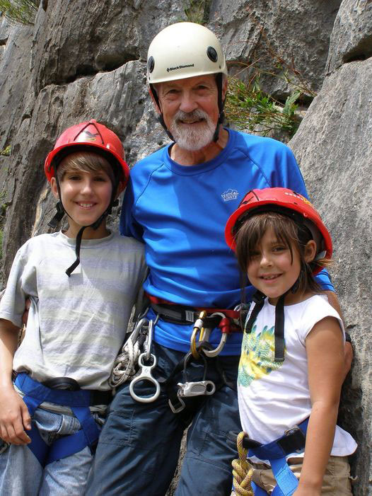 Armando stands besides two young children in climbing gear at the base of a cliff. All three are smiling.